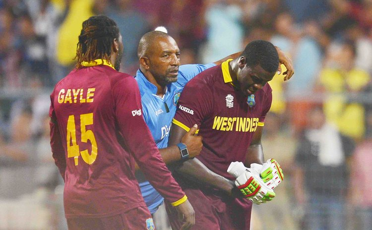 Gayle and  coach Simmons congratulate Braithwaite at the end of the World T20 Finals