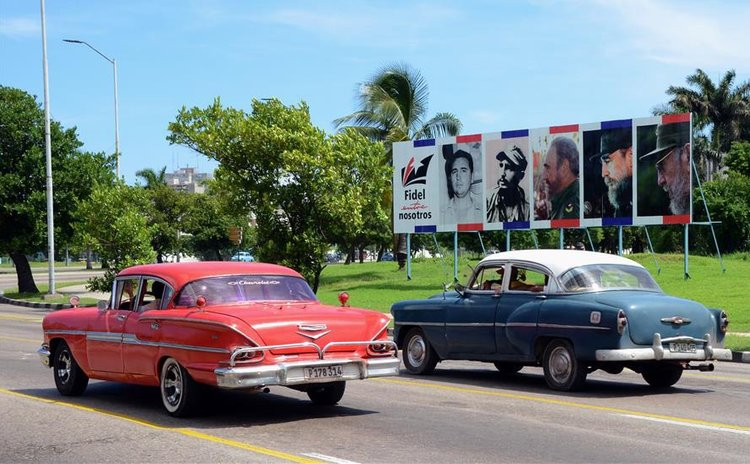 Image taken on Aug. 11, 2016 shows vehicles passing a billboard featuring retrospective photos of Fidel Castro, in Havana, capital of Cuba