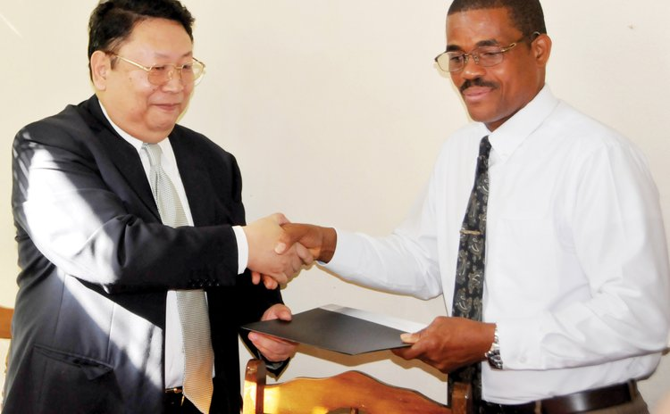 Chinese Ambasador Jiangning ,right exchange agreement with Education Minister Petter St .Jean
