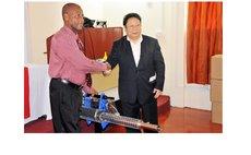 Chinese Ambassador Li Jiangning, right , hands fooging machine to Parliamentary Secretary Stevenson