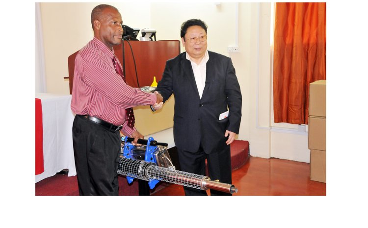 Chinese Ambassador Li Jiangning, right , hands fooging machine to Parliamentary Secretary Stevenson