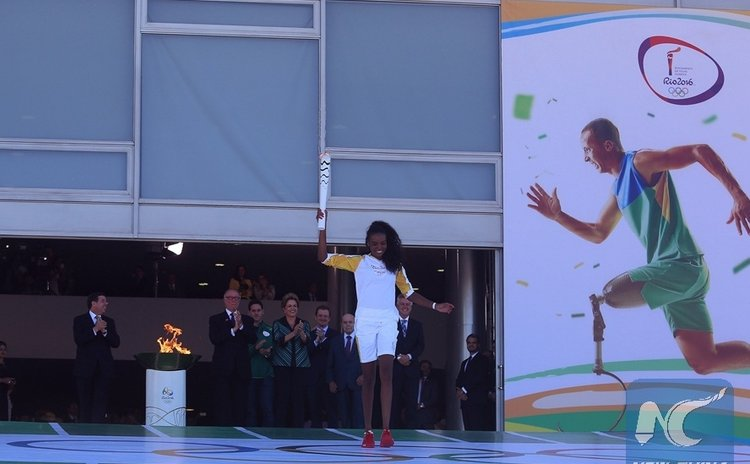 Brazilian volleyball player and the first torchbearer in Brazil, Fabiana Claudino, leaves the Planalto Palace with the Olympic torch, in Brasilia, Brazil on May 3, 2016. (Xinhua/Rahel Patrasso)