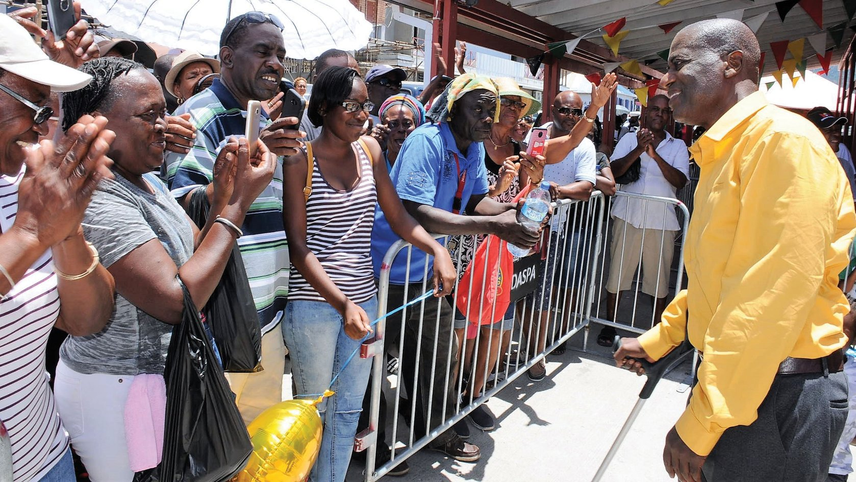 Dr Sam Christian  greets well-wishers at the ferry terminal in Roseau