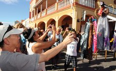 Cruise visitors take pictures of carnival band at the Roseau Cruise Ship berth