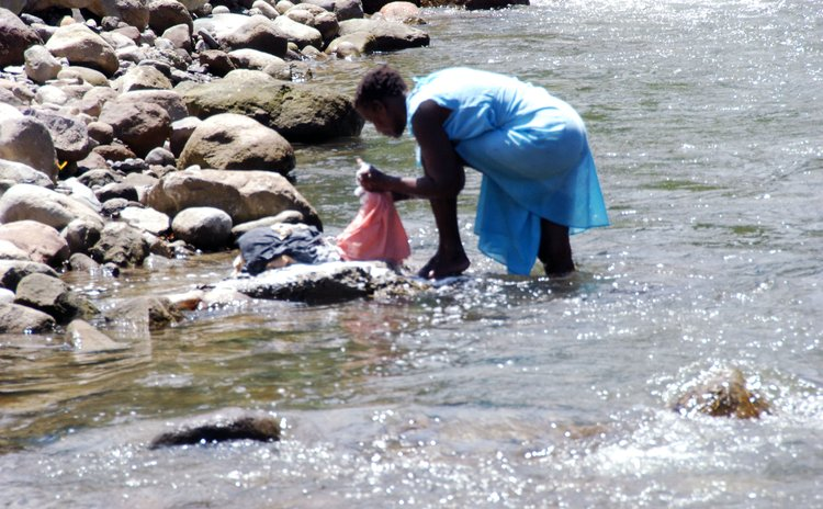 A woman washes her clothes in the Roseau River
