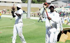 Shane Shillingford, right, wave to fans after a West Indies win at the Windsor Park