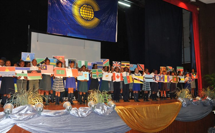 Students hold up maps of Commonwealth countries at the Arawak House of Culture during Commonwealth Day Ceremony