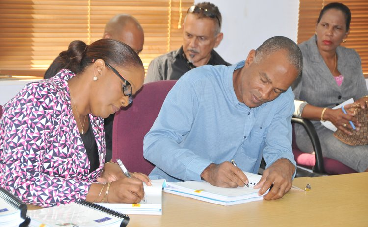 Roberts, left, and contractor sign documents