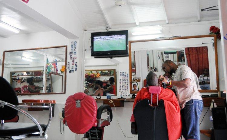A Haitian barber shaves a client at a shop on Hillsborough Street