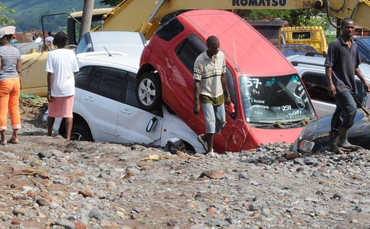 Men walk near buried cars at Massacre