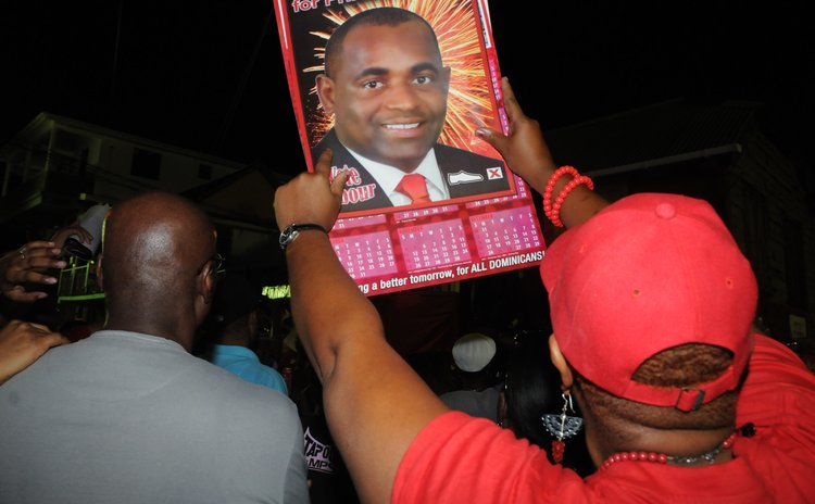 Asupporter holds up a poster of Skerrit at a party rally