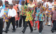 A young boy marches on Independence Street during the National Dress Parade