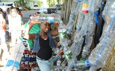 Girl shows plastic bottles at the Dominica Climate Change Day of Action at the Botanic Gardens, Roseau on Saturday November 28, 2015