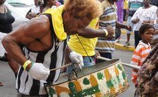Man plays rust steel pan at the opening of Carnival