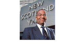 David Michael poses before UK Scotland Yard sign