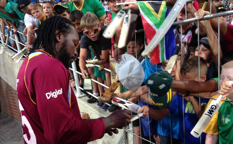 Chris Gayle signs autographs after the game