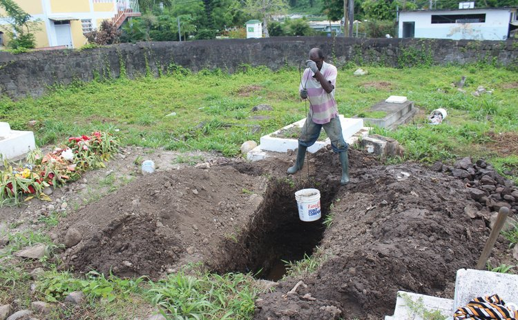 Gravedigger removes buckets of water from grave at Catholic Cemetery , Roseau