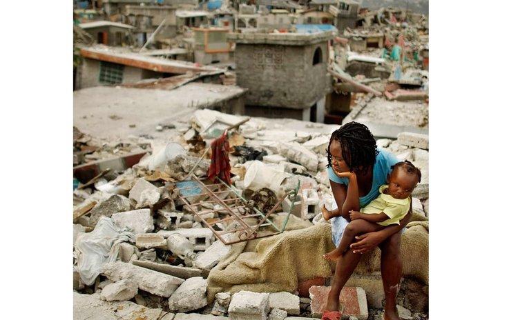 Woman and child sits on rocks after massive earthquake- Haiti