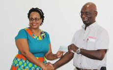 John Lewis hands over cheque to representative of the Dominica Infirmary