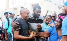 Supporters hug Spags John after he was released on bail