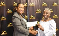 Carol Jno Charles, right, receives prize from NBD's Lisa Latouche