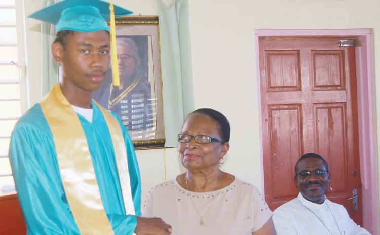 Valedictorian Jno Baptiste receives award from Mrs. Leevy