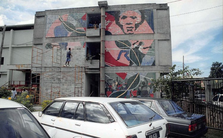 Man paints over mural of 29 May 1979 on Treasury Building in Roseau