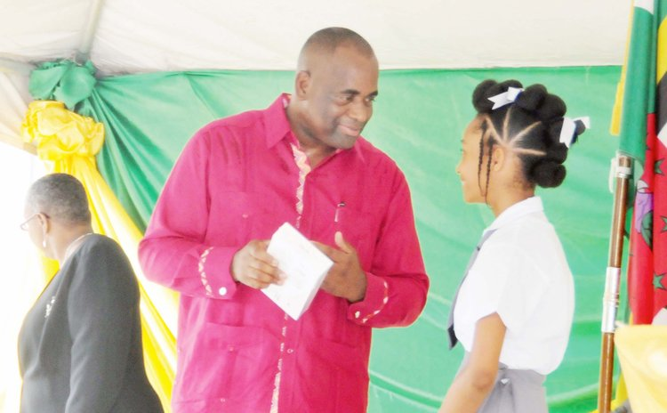 Prime Minister Skerrit hands tablet to student at the Pierre Charles Secondary School