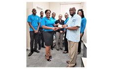 Gina Severin , Republic Bank manager hands over cheque to Grotto president Ainsworth Irish