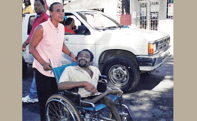 Founder of DADP Reggie Rolle in wheelchair being pushed by wife Nathalie