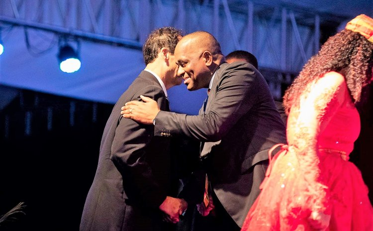 Prime Minister Skerrit hugs Popone, his father-in-law after Popone receives award