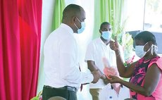 Prime Minister Skerrit hands over keys to a house to Grand Bay woman