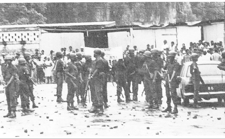 After the tear gas and the stones members of the Defence Force stand near Government Headquarters on Kennedy Avenue