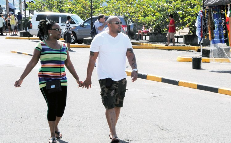 Tourists hold hands on the Roseau Bay Front