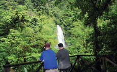 Two tourists look at one of the two Trafalgar waterfalls