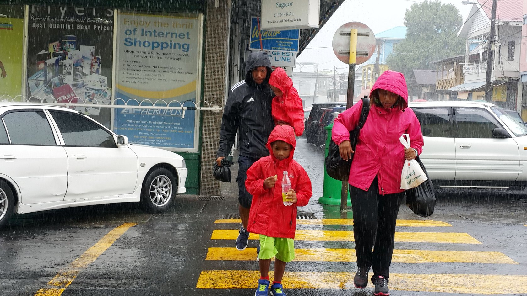 Walking in the rain with the ones we love... near HHV Whitchurch supermarket in Roseau