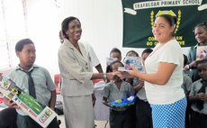 Ms White, centre, presents gifts to Trafalgar School
