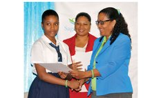 Ms Rolle of Sagicor hands prize to St Martin's School Student Ms Francois